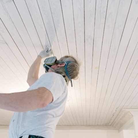Maler der Farbe benutzt und sich mit einem Atemschutz schützt