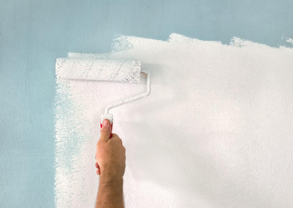 Farbrolle mit weißer Farbe die auf blaue Wand gestrichen wird