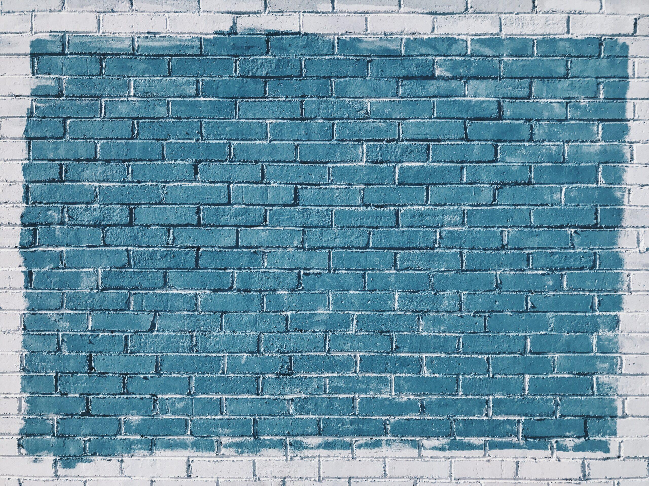 Blaue Farbe auf weißer Steinwand