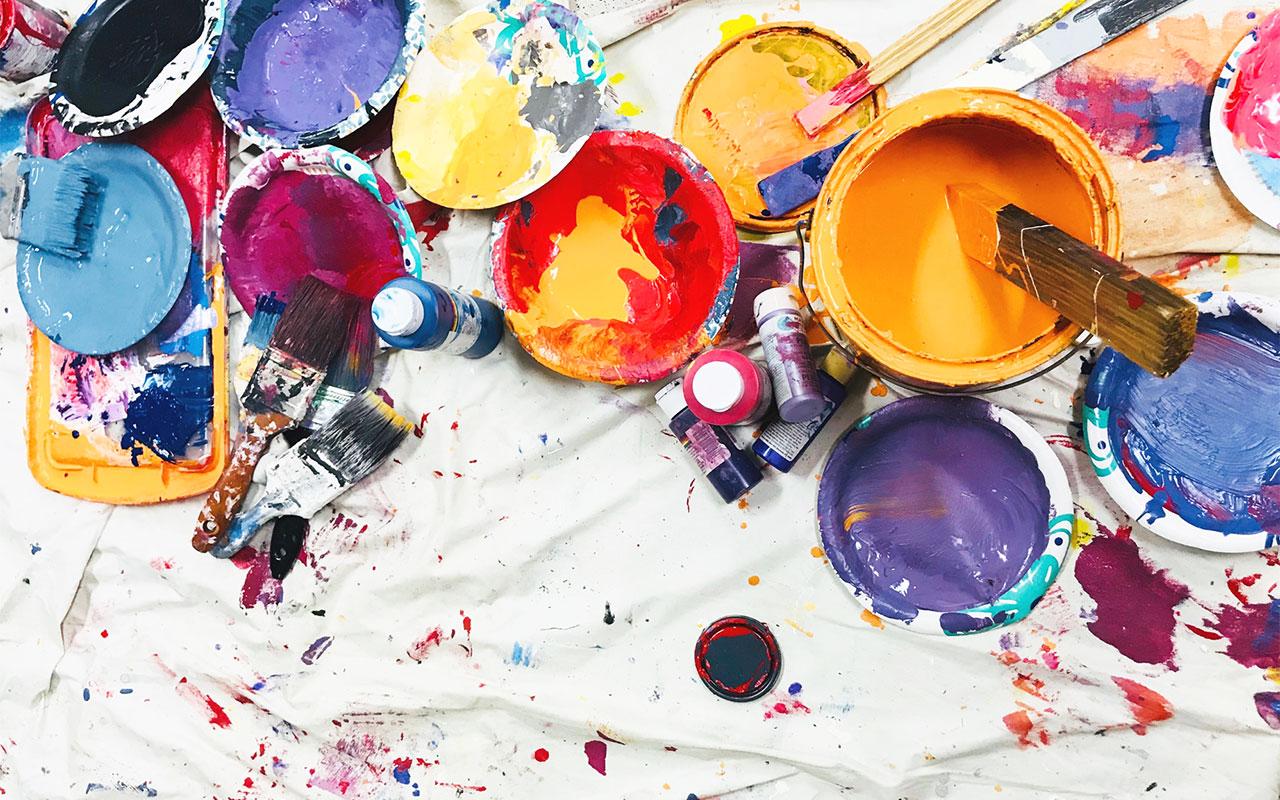 Farbreste und Farbeimer auf schmutzigem Untergrund